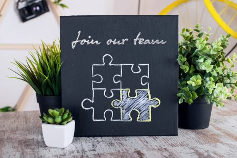 Join our team written on a chalkboard with plants around it