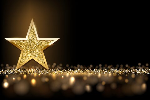 Image of golden star and glitter against black background
