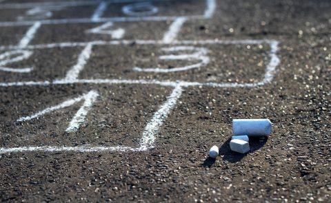 General image of chalk on playground with hopscotch drawn in background